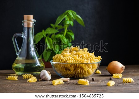 raw ingredients for cooking italian pasta. fusilli   garlic basil olive oil onion on wooden table dark background copy space