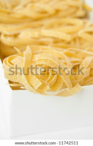 Raw italian pasta in a white box - stock photo