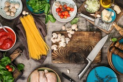 Raw Italian spaghetti and ingredients for cooking pasta on a wooden table, top view