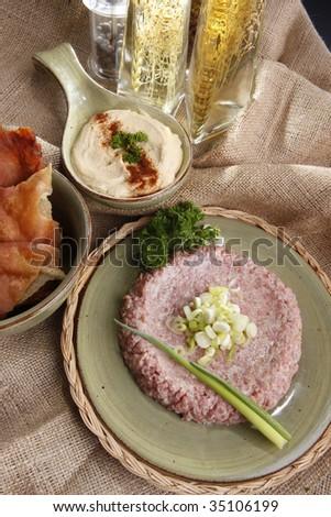 Raw kibbe, fried pitta bread, hummus tahine and seasoned olive oils