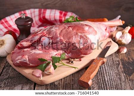 raw lamb leg on board