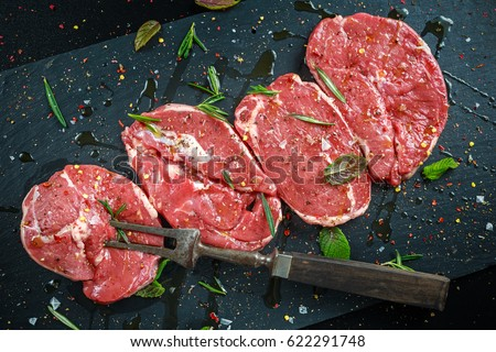 Raw Lamb leg steaks on stone chopping board with vintage fork served with sea salt and chillie flakes, rosemary and mint #622291748