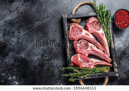 Raw lamb meat chops steaks in a wooden tray. Black background. Top view. Copy space.