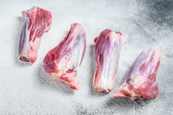 Raw lamb shanks meat on stone table. White background. Top view