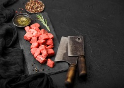 Raw lean diced casserole beef pork steak on chopping board with vintage meat hatchets on stone background. Salt and pepper