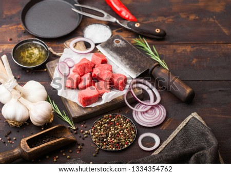 Raw lean diced casserole beef pork steak with vintage meat hatchet and fork on wooden background. Salt and pepper with fresh rosemary, red onion and garlic. #1334354762