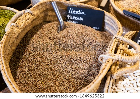 Raw lentils in wicker basket on market counter. Concept of healthy and nutritious food