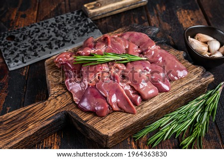 Raw liver chicken offals meat on a wooden cutting board with butcher cleaver. Dark wooden background. Top view Foto stock ©