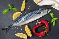 Raw mackerel with spices, herbs and sea salt on black textured table top view.