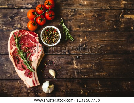 Raw marbled meat steak, pepper, herbs, tomato, old wooden background. Space for text. Beef Rib eye steak ready for cooking. Top view. Copy space. Ingredients, meat roasting. Ribeye meat steak. Closeup