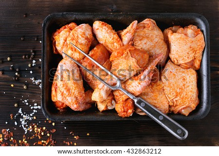 Raw Marinated chicken meat wings and legs for BBQ, served in plastic box with seasoning and vintage meat fork over dark wooden background. Top view