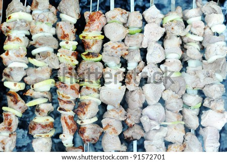 Raw meat and onions on skewers