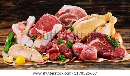 Raw meat assortment, beef, chicken, turkey, decorated with greens and vegetables, placed on cooking paper on wooden table #1198525687