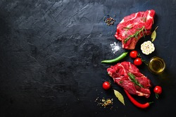 Raw meat, beef steak on a stone cutting board with rosemary, spices, salt, oil, cherry tomatoes, hot pepper and herbs