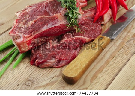 raw meat : boned fresh lamb ribs served with thyme , red chili pepper , and green onion on wooden board