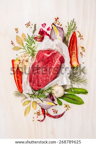 Raw meat, composing with herbs,spices and seasoning on white wooden background, ingredients for cooking, top view