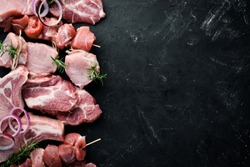Raw meat for barbecue. Meat with spices and herbs. On a black stone background. Top view. Free copy space.
