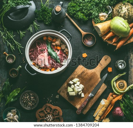 Raw meat in cooking pot on kitchen table background with vegetables , seasoning and kitchen utensils, top view. Flat lay. Meat dishes recipes. Broth, meat bone stock or soup cooking preparation