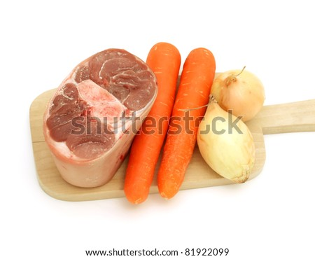 raw meat of a leg and vegetables on kitchen bread isolated on white background