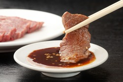Raw meat on a plate and grilled meat with sauce