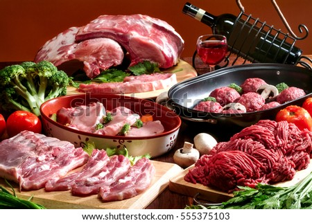 Raw meat on wooden board,vegetables, glass of wine and bottle with clipping path label. #555375103