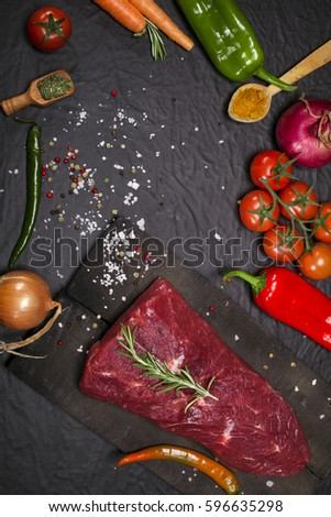 Raw meat. Raw beef steak on a cutting board with herbs and vegetables. #596635298