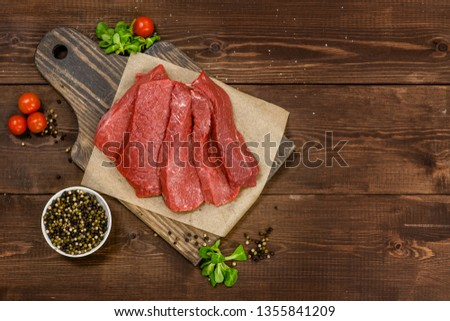 Raw meat. Raw beef steak on a cutting board with vegetables. Top view