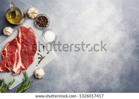 Raw meat. Raw beef steak on with rosemary, pepper, garlic, olive oil and salt. Top view. left edge, copy space.