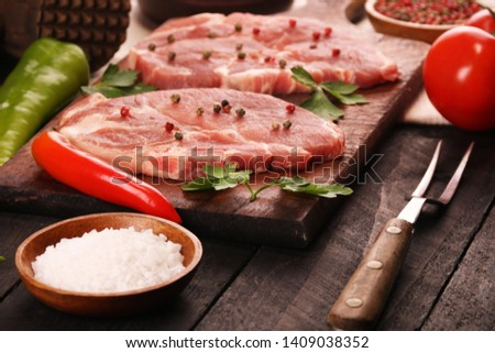 Raw meat. Raw pork steak on a wooden cutting board with vegetables, peppers, tomato, salt and spices on a black background