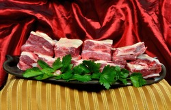 Raw meat ribs on a black clay plate, gold and red silk fabric background. Raw Organic Beef Short Ribs decorated with green persil leaves