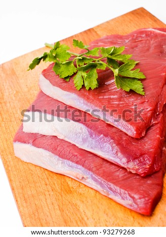 Raw meat slices on board with parsley