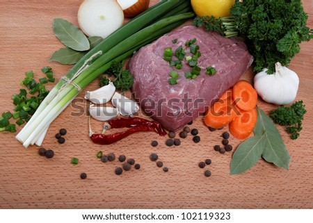 raw meat, vegetables and spices isolated on a wooden table.