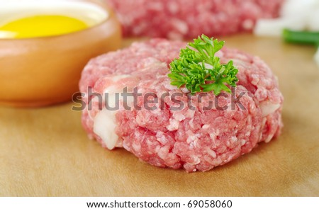 Raw meatball garnished with a parsley leaf and a raw egg, green onion pieces and mincemeat in the back (Very Shallow Depth of Field, Focus on the front of the meatball and the leaf)