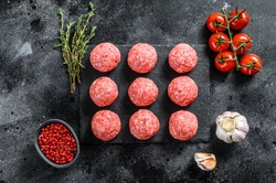 Raw meatballs made from ground beef. Black background. Top view