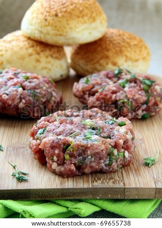 raw minced meat for hamburgers on a wooden board