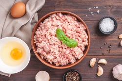 Raw minced meat in bowl on wooden table and ingredients. Ground meat with ingredients for cooking on dark background with copy space. Top view or flat lay