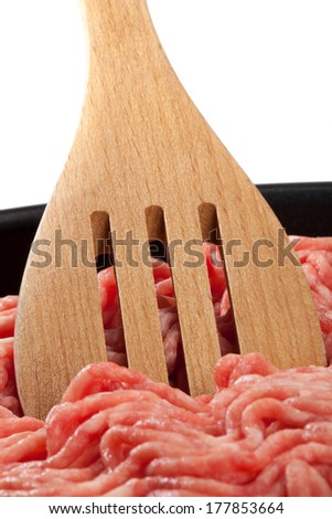 Raw minced meat with a wooden spoon in a pan.
