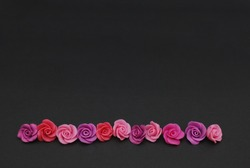 Raw Mix of pink and Peach Fake Plastic Mini rosess Flowers Black Background copy space. Craft, Art, Hobby concept.
