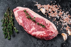 Raw new york strip steak on a butcher table with salt and thyme. Black background. Top view