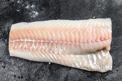 Raw Norwegian skrei cod fish fillet. Black background. Top view