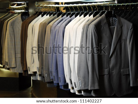 Raw of different colors man's jackets hanging  on apparel. - stock photo