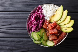 Raw Organic Ahi Tuna Poke Bowl with Rice and Veggies close-up on the table. Top view from above horizontal