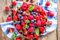 Raw Organic Assorted Various Fresh Berries with Blueberries Raspberries and Strawberries on rustic wooden background