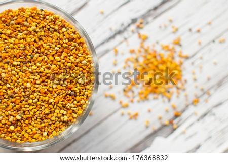 raw organic bee pollen over wooden board