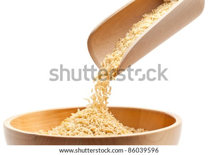 Raw organic brown rice filled into wooden bowl over white background