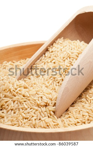 Raw organic brown rice in wooden bowl over white background