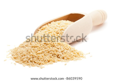 Raw organic brown rice in wooden scoop over white background - stock photo