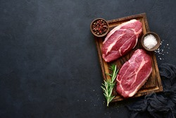 Raw organic marbled beef steaks with spices  on a wooden cutting board on a  black slate, stone or concrete background. Top view with copy space.