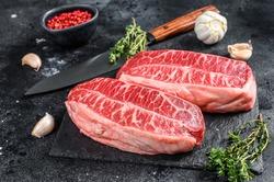 Raw organic meat Twagyu oyster top blade steak. Black background. Top view.