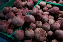 Raw organic red beets. A bunch of natural vegetables in green containers at the farmers market. Food supply.